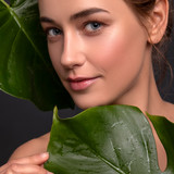 Cute ordinary young woman posing with monstera tropical leafs. Fresh clean skin with flawless texture. Skin care beauty cosmetology concept. Space for text - 241691066