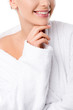 Leinwanddruck Bild - cropped view of woman in bathrobe touching chin isolated on white