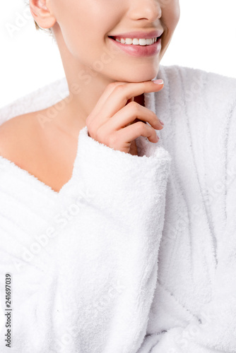 Leinwanddruck Bild cropped view of woman in bathrobe touching chin isolated on white