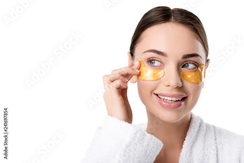 Leinwanddruck Bild beautiful smiling woman with golden eye patches touching face isolated on white