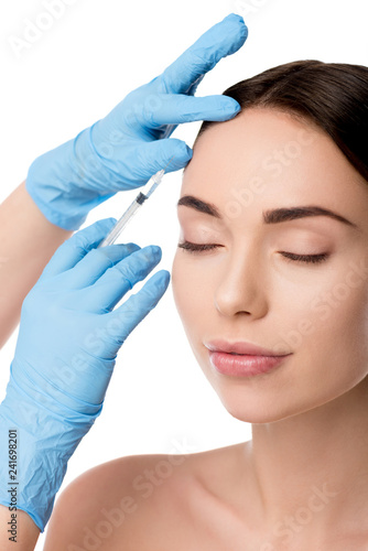 Leinwanddruck Bild doctor in latex gloves giving beauty injection with syringe to woman isolated on white
