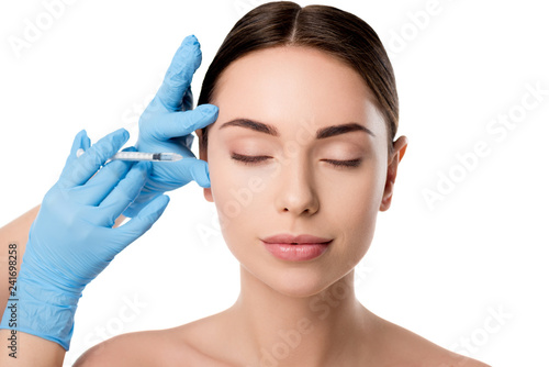 Leinwanddruck Bild doctor in latex gloves giving beauty injection with syringe to woman with eyes closed isolated on white