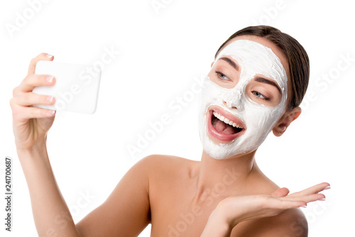 Leinwanddruck Bild happy woman with facial skin care mask taking selfie on smartphone isolated on white