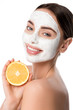 Leinwanddruck Bild - beautiful smiling woman with facial skin care mask holding orange and looking at camera isolated on white