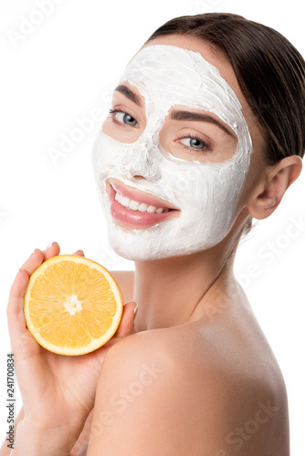 Leinwanddruck Bild beautiful smiling woman with facial skin care mask holding orange and looking at camera isolated on white