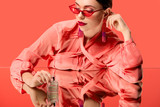 stylish woman in blouse and red sunglasses posing with perfume bottle and mirror reflection isolated on living coral - 241702026