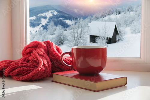 Foto Murales cup with a hot drink on the windowsill in the background of a winter city. Focus on the edge of the cup