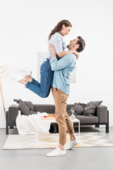 happy man in casual clothes holding woman in living room