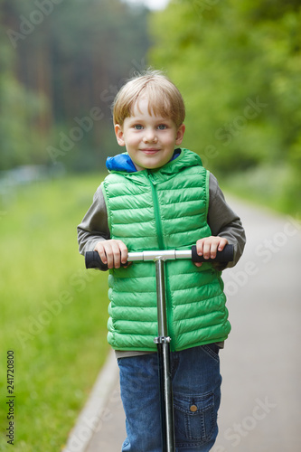 Little blond boy riding a scooter in a park