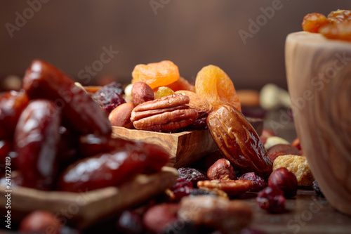 Leinwandbild Motiv Various dried fruits and nuts in wooden dish.