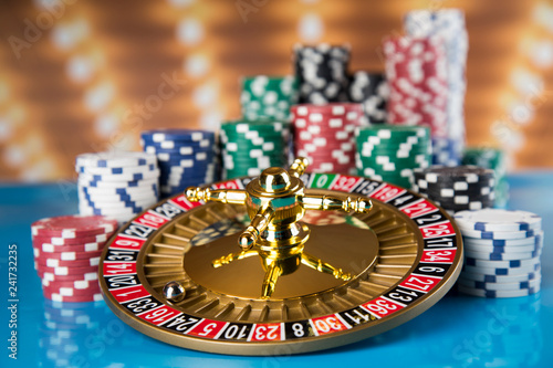 Poker Chips, Roulette wheel in motion, casino background - 241732235