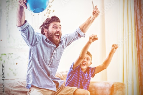 Excited father and son watching television - 241739471