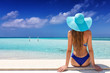 Leinwanddruck Bild - Strandurlaub Konzept: attraktive Frau im Bikini und mit Sonnenhut schaut auf einen tropischen Strand mit türkisem Meer und blauem Himmel