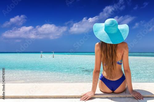 Leinwanddruck Bild Strandurlaub Konzept: attraktive Frau im Bikini und mit Sonnenhut schaut auf einen tropischen Strand mit türkisem Meer und blauem Himmel