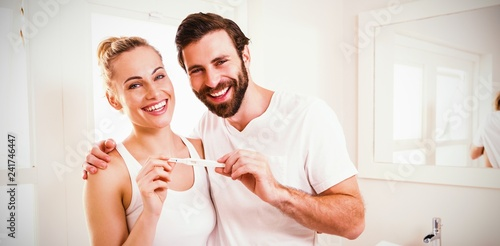 Portrait of happy couple checking pregnancy test - 241746447