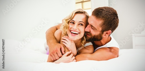 Leinwanddruck Bild Young couple embracing on bed