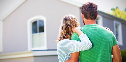 Couple standing against house