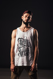 Portrait of a bearded man a hip hop dancer or bboy in urban style clothes and with inscription
