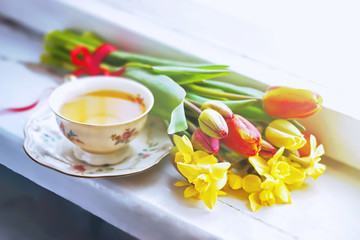 Tulips, daffodils and a cup of tea on the wooden windowsill, selective focus.