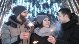 Friends celebrating New Year outdoors, keeps sparklers, lights in the blur in the background. New Year and Christmas concept - 241765624