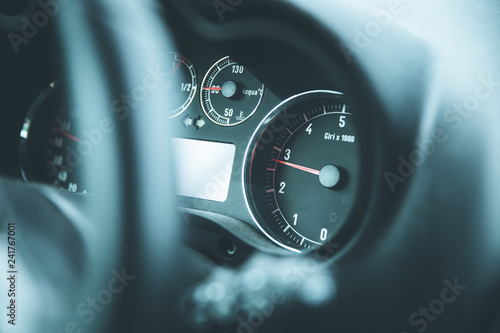 Sports car dashboard and steering wheel with tachometer and fuel indicator