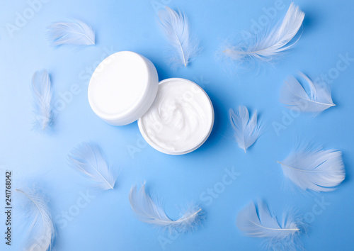 Leinwanddruck Bild White jar cream and feather tendernessn beauty on blue background, top view