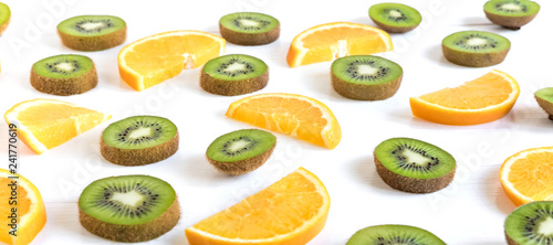 Pattern with oranges and kiwi slices on a white wooden background. The basis for the booklet, the background for the banner. Basis for design with tropical fruits - 241770619