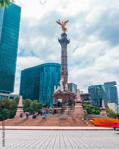 Foto Murales Long shot of the most important landmark in Mexico: The angel of Independence, buildings and people walking around on blue sky