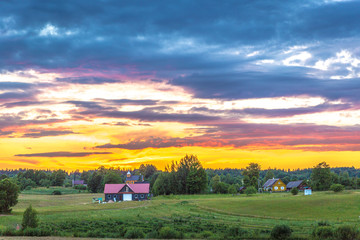 Beutiful colorful sunset in Estonia with farm houses and a pine tree forest in Europe