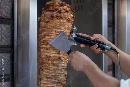 Cocinero partiendo carne de kebab para servir © Trepalio