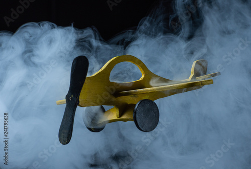 yellow toy airplane flying in cold fog and Blizzard as a symbol of delivery of mail, cargo and news