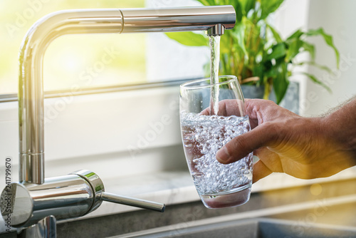 Hand holding a glass of water poured from the kitchen faucet