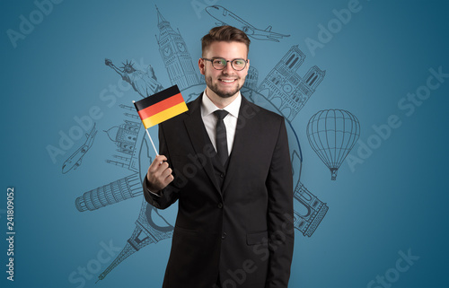Leinwanddruck Bild Elegant man with sightseeing concept on the background  and flag on his hand