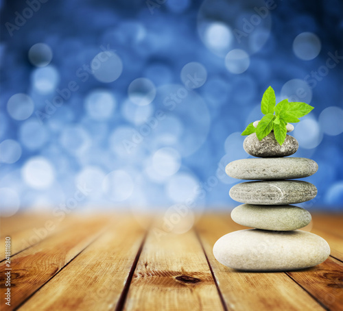 zen stones on the old wood and abstract blue background