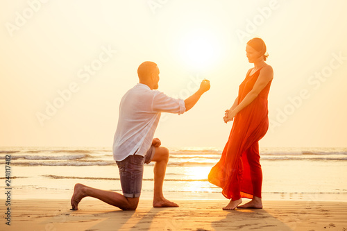 Leinwandbild Motiv male making proposal with engagement ring to his girlfriend at sea beach.Valentine's Day February 14 wedding concept.man on his knee making a marriage proposal to his woman sunset romantic I said yes