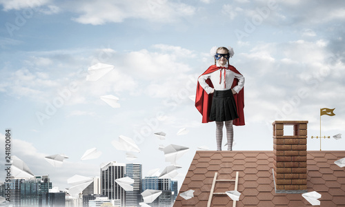 Girl power concept with kid wearing cape and mask and playing gu