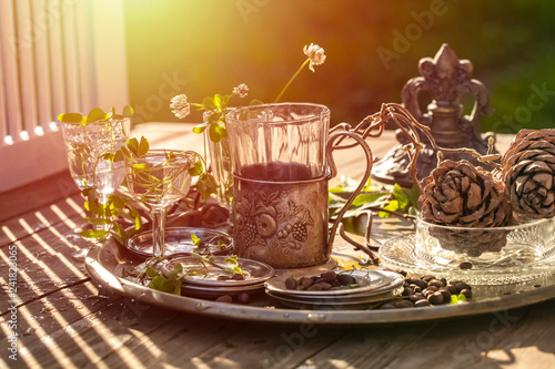green sprouts in glass goblets with water and pine cones with nuts on a tray, under the rays of the morning sun. copy space