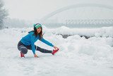 Fototapeta Panele - Young woman stretching legs on snowy day in the city © djile