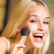 Leinwanddruck Bild - Young blond woman with makeup brush at home
