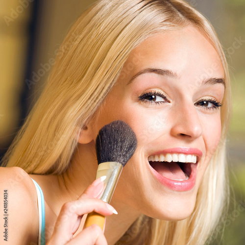 Leinwanddruck Bild Young blond woman with makeup brush at home