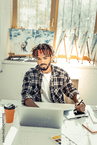 Young creative artist drinking some coffee and working on laptop