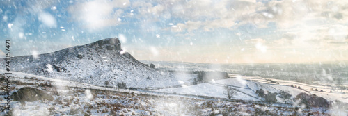 Stunning Winter panoramic landscape snow covered countryside with beautiful sky and clouds in heavy snow storm