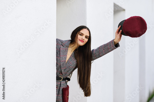 Spain, Andalusia, Granada. Young beautiful girl with very long hair looking at camera wearing winter coat and cap outdoors. Lifestyle and fashion concept.