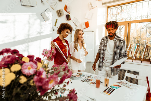 Foto Murales Art students standing in decorated studio near white table with flowers
