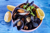 Delicious opened black mussels with sprigs of parsley and slice of lemon in a bowl on a blue wooden background, top view - 241873815