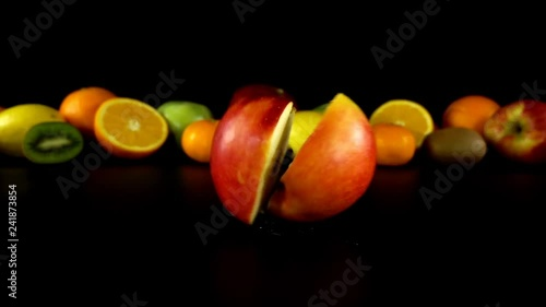 Falling of apple against the background of fruit. Slow motion.