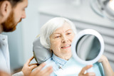 Happy elderly woman enjoying her beautiful toothy smile looking to the mirror in the dental office - 241876642