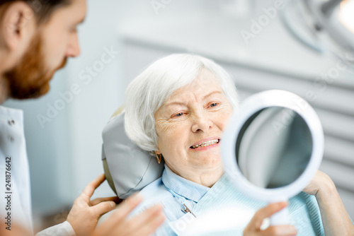 obraz PCV Happy elderly woman enjoying her beautiful toothy smile looking to the mirror in the dental office