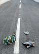 Broken skateboard on dark asphalt street