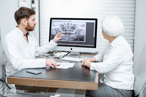 Leinwanddruck Bild Senior woman patient during the medical consultation with dentist showing dental x-ray on the monitor